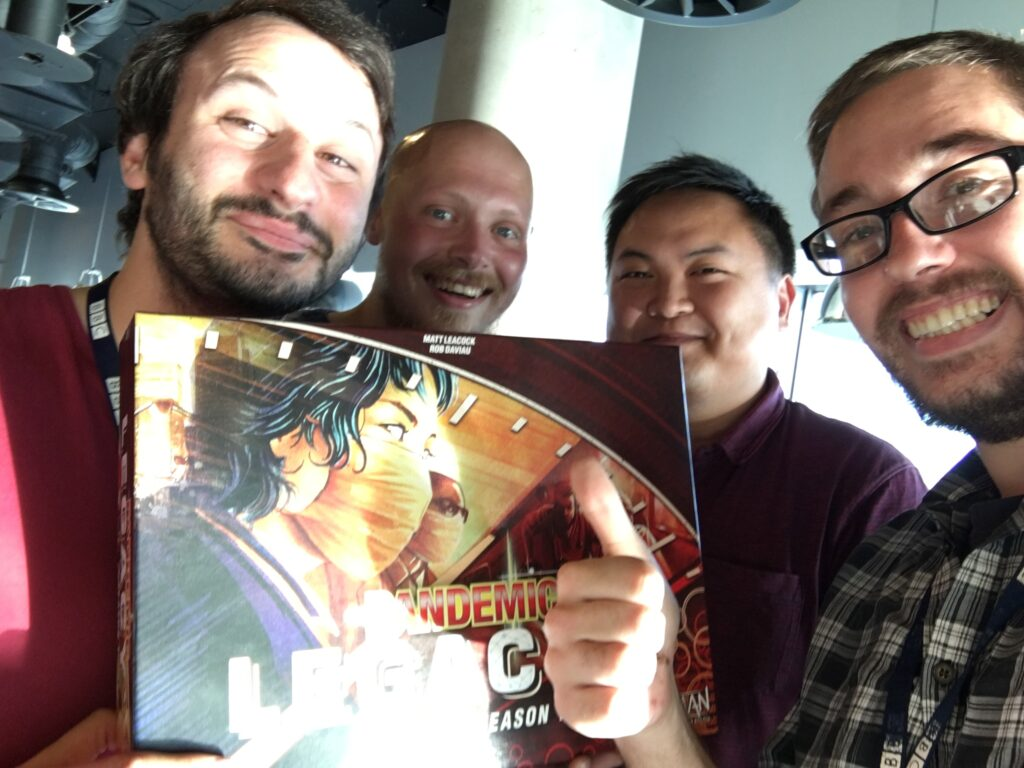Si and three work friends holding a copy of the boardgame, Pandemic Legacy